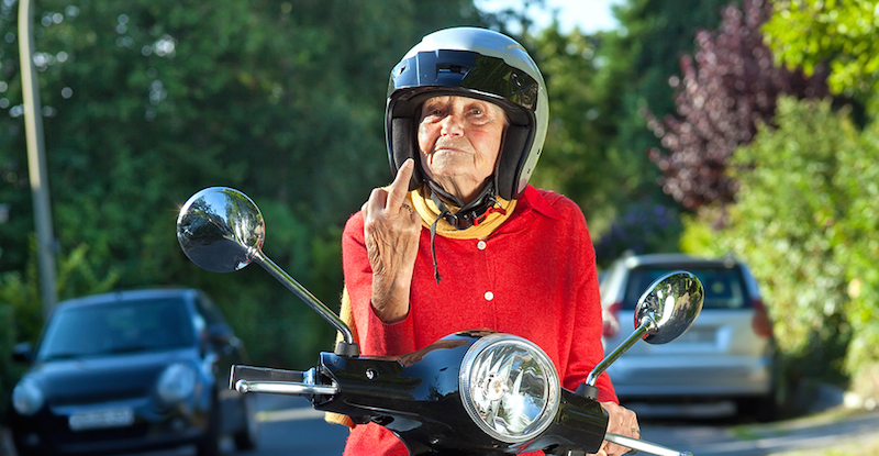Visitor's guide America. Senior woman on scooter showing road rage