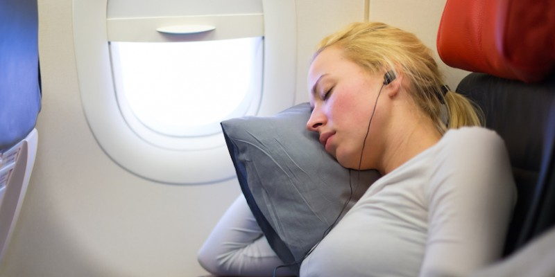 Blonde woman sleeping on plane in Mind Your Own Business Class.