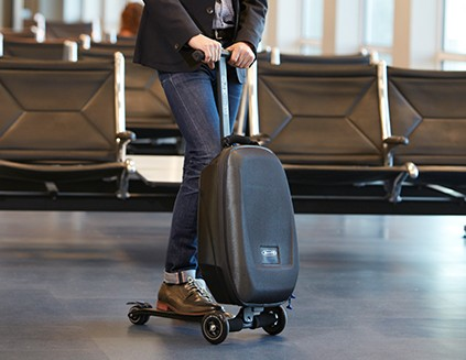Man riding carryon bag scooter